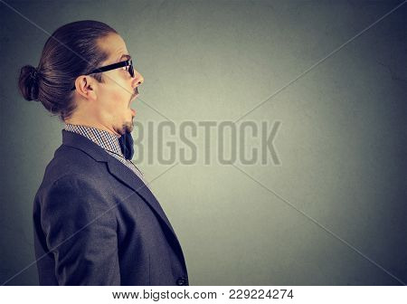 Side View Of Man In Suit Standing With Mouth Opened On Gray Looking Amazed And Shocked.