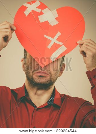 Bad Relationships, Breaking Up, Sadness Emotions Concept. Adult Man Holding Broken Heart, Covering H