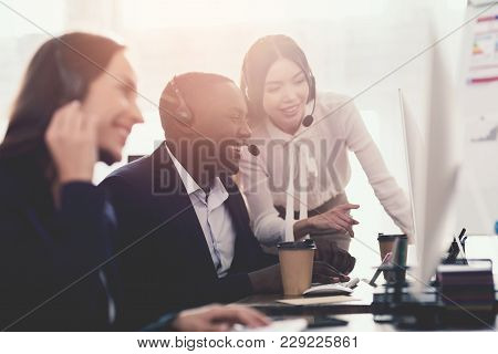 A Girl Shows Her Colleague In The Call Center Something On The Computer Screen. They Are Operators O