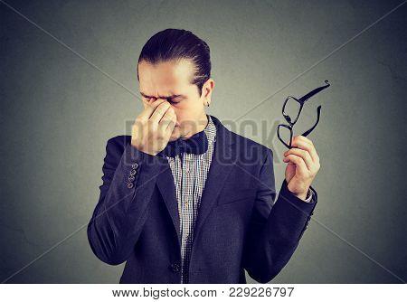 Elegant Man Taking Off Glasses And Rubbing Nose Bridge Looking Tired.