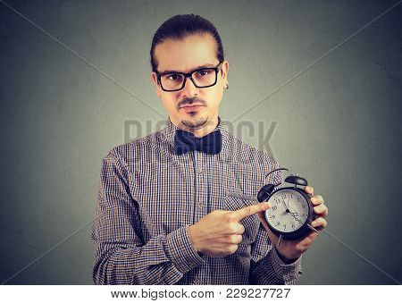 Formal Man In Eyeglasses Reminding About Punctuality Pointing At Clock And Looking At Camera.