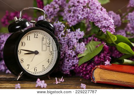 Black Alarm Clock, An Old Book And Lilac Flowers As A Background. Spring Time Change. Good Morning H