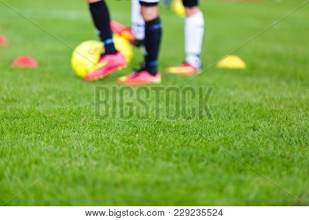 Out Of Focus Shot Of Soccer Balls And Legs Of Soccer Players During A Soccer Training Session On Gre