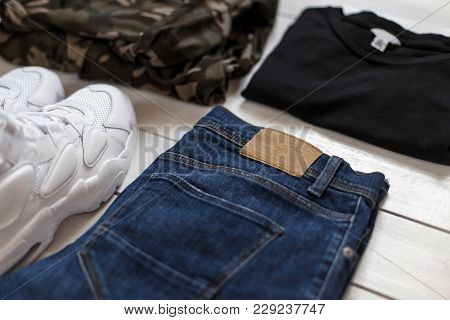 Men's Summer Collection Of Fashion Clothes On A White Wooden Background. Sneakers, T-shirt, Military