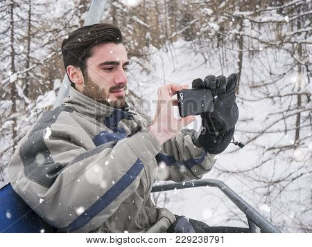 Handsome Young Man Using Smarpthone To Take Photographs Of The Landscape, While Sitting On Chairlift