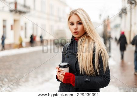 Beautiful Young Blonde Woman With Coffee In A Fashion Winter Coat In The City