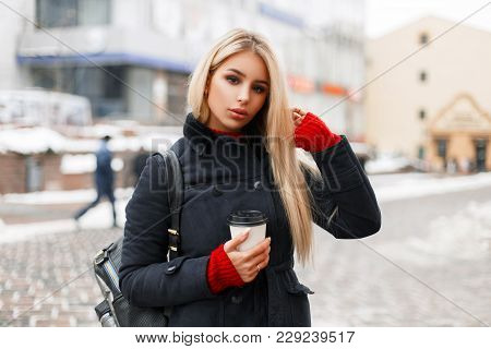 Pretty Young Blond Woman Model With Coffee In A Fashion Coat With A Bag On The Street In The City