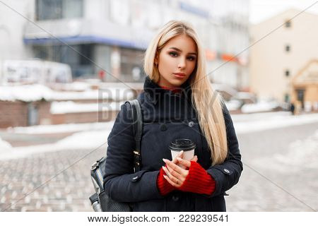 Beautiful Fashionable Girl With Coffee In A Trendy Winter Coat With A Bag Walking In The City
