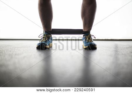 Legs Of Man Training With Elastic Tape At The Ankles
