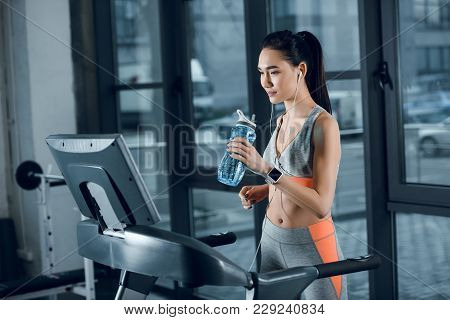 Young Athletic Sportswoman Drinking Water While Jogging On Treadmill At Gym