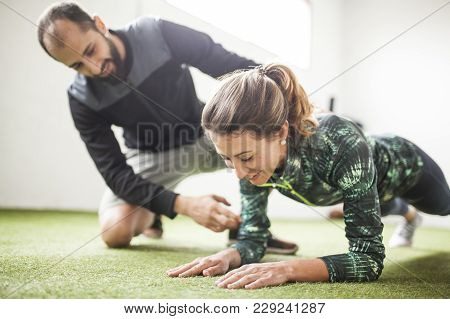 Personal Trainer Training Woman Under Window On The Green Floor