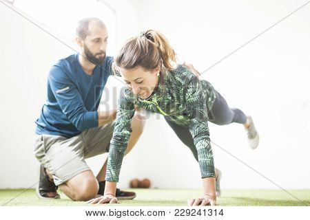 Personal Trainer Training Woman Under Window On The Floor