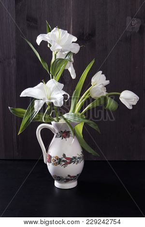 Wedding Bouquet Of Lily Abd Tulips In A Jug On A Black Background