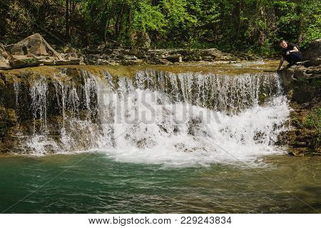 A Young Man Sits Near A Small Waterfall And Clear Mountain River Zhane Near The Village Vozrozhdenie