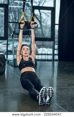 Young Fit Woman Working Out With Suspension Straps At Gym