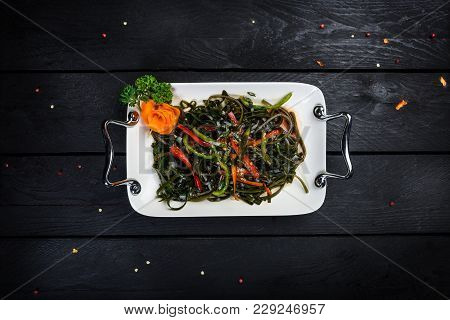 Chinese Salad With Sea Kale On The White Plate On Black Wooden Background, Top View