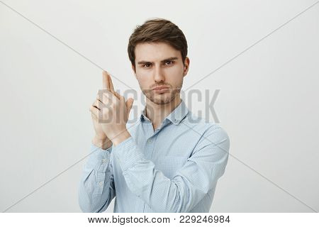 Handsome Young Male Office Worker, Wearing Formal Shirt And Making Gun Gesture, Raising Hands As If