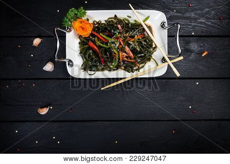 Chinese Salad With Sea Kale On The White Plate Served With Chopsticks. On Black Wooden Background, T