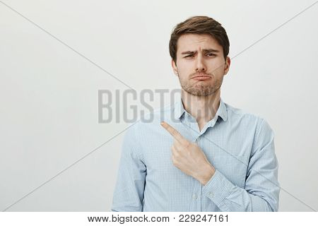 Such Shame I Missed All Fun. Portrait Of Handsome Sad Caucasian Guy Pointing Left With Index Finger