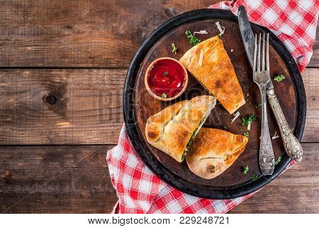 Italian Food, Closed Pizza Calzone With Spinach And Cheese, Wooden Background, Copy Space Top View