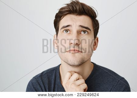 Pensive Dreamy Male Student Posing Against Gray Background, Looks Thoughtfully Upwards. Attractive B