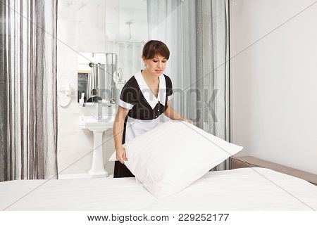 Pillows Should Be White Like Snow. Good-looking Near Woman In Maid Uniform Making Bed, Working As Ho