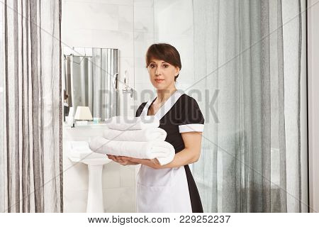Sir, I Will Put Extra Towels In Bathroom. Portrait Of Woman In Maid Uniform Standing With White Hote