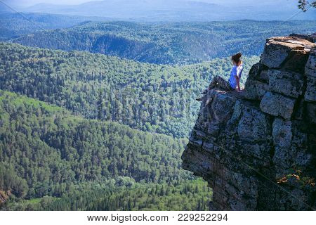 Young Lady Hiker Sitting On Top Of A Mountain On On High Altitude And Enjoy Amazing View. - Wide Sho