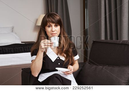 Housekeeper On Guard Of Cleanness. Indoor Shot Of Calm And Confident Maid In Uniform Sitting On Sofa