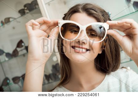 Pretty Brunette Girl Smiling, Trying On Sunglasses In Optical Shop. Charming Feminine Woman In Sungl