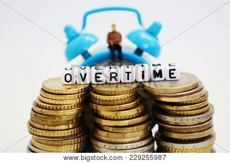 Businessman Figurine With Laptop Sitting On Classic Blue Clock, Behind The Piles Of Cash Money, Paid