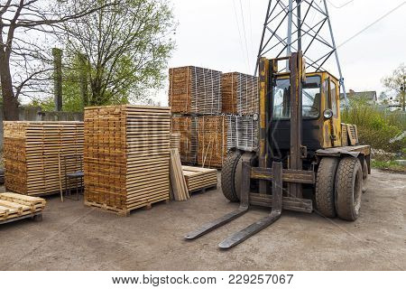 Large Lift Truck And Stacks Of New Wooden Boards And Studs At The Lumber Yard. Wooden Plates On Pile