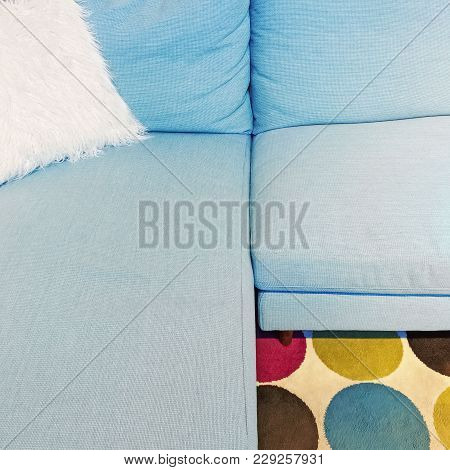 Fluffy White Cushion On A Blue Textile Sofa. Modern Furniture With Retro Feel.