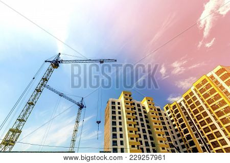 Crane And High Rise Building Under Construction Against Blue Sky. Modern Architecture Background