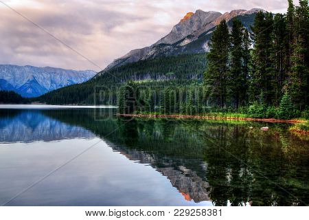 Sunset At Two Jack Lake In Banff National Park With Sunlit Mountain Ranges In The Background Reflect