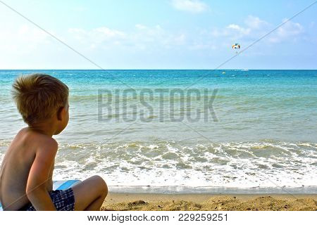 Little Boy Sits On The Beach And Looks At The Sea And Parachute In The Sky