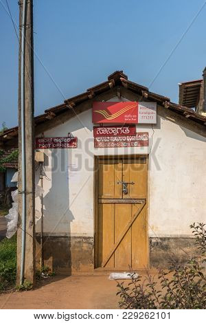 Madikeri, India - October 31, 2013: Public Post Office Shows Closed Brown Wooden Door Set In White W