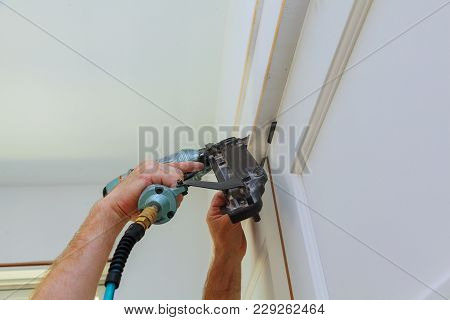 Do It Yourself Home Owner Repairing Door Frame Molding With Nail Gun, Close Up On Hand And Nail Gun.