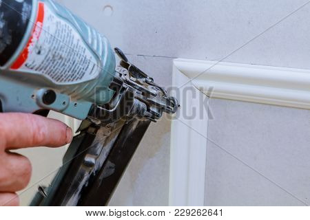 Carpenter Brad Using Nail Gun To Moulding Trim, With The Warning Label That All Power Tools