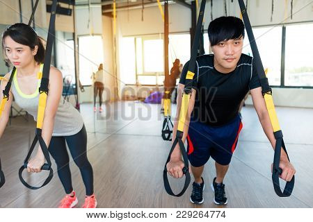 Strong Asian Male Coach Showing How To Train With Trx Suspension Training System With His Charming S