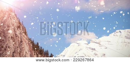Snow falling against snow capped mountain against sky