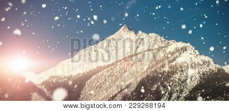 Snow falling against snowy mountain range against blue sky