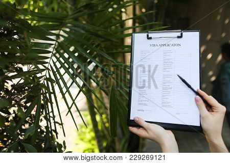 Beautiful Hands Of Girl Suggest Signing An Empty Paper Or Contract On Background Of Palms And Sun. C