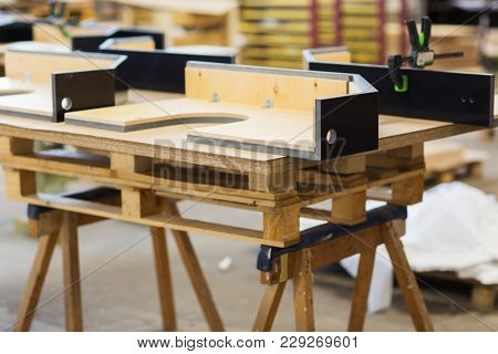 production, manufacture and woodworking industry concept - furniture items on workbench at workshop