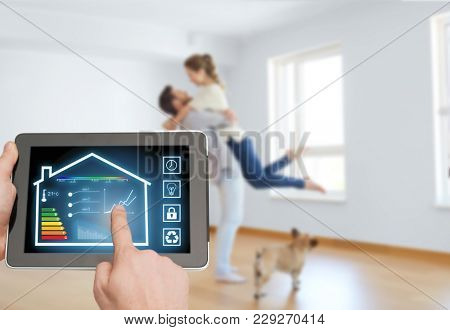 smart home and technology concept - close up of male hands pointing finger to tablet pc computer with house settings on screen and in room background