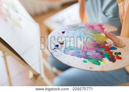 art, creativity and people concept - close up of artist with paint on palette painting at studio