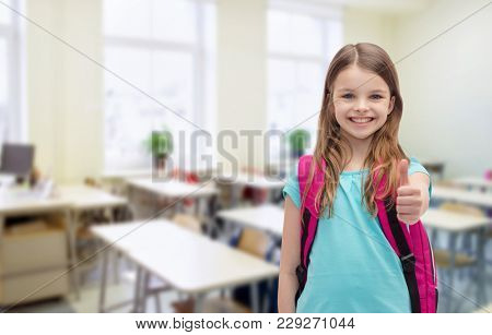 education, gesture and school concept - happy and smiling little girl with school bag showing thumbs up over classroom background