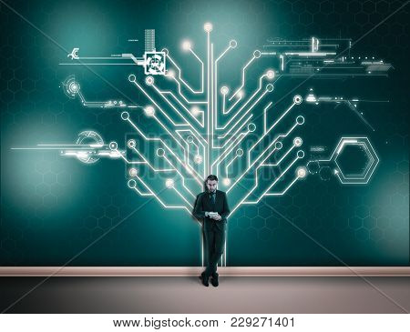 Businessman Working On His Phone In Front Of A Wall With A Circuit Board Tree . The Concept Of Worki