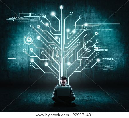 Businessman Working On His Laptop In Front Of A Wall With A Circuit Board Tree . The Concept Of Work