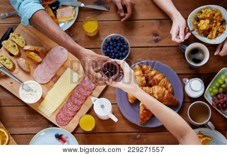 food, eating and family concept - group of people sharing jam for breakfast at wooden table